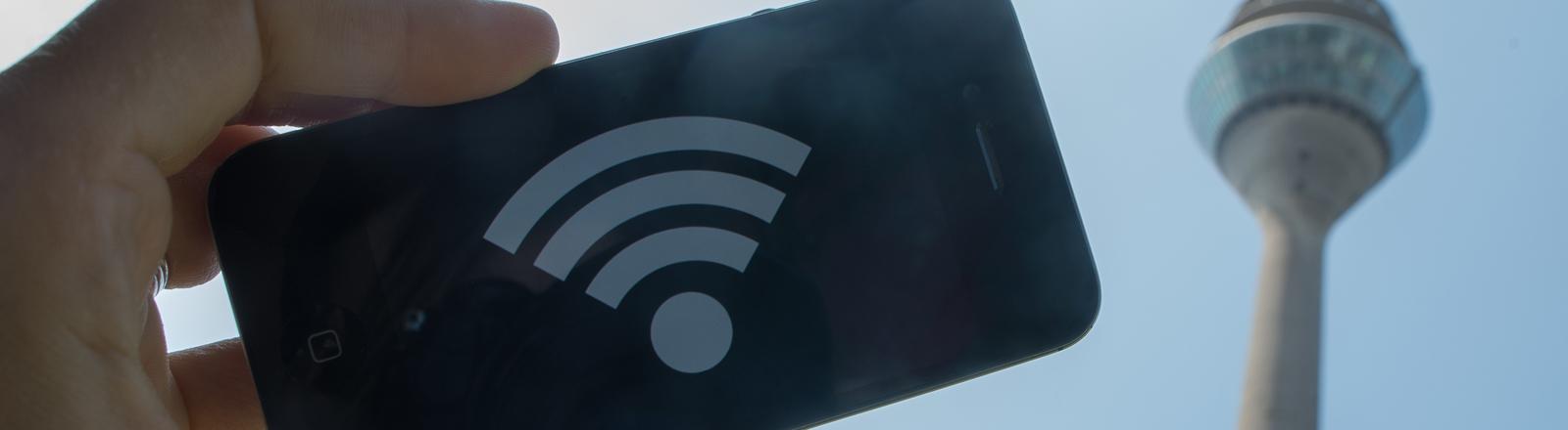 Ein WLAN-Symbol ist am 16.07.2015 in Düsseldorf (Nordrhein-Westfalen) vor dem Rheinturm auf einem Smartphone zu sehen.