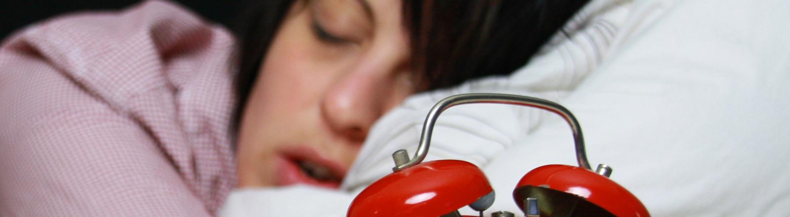 Ein Frau im Bett neben einem Wecker
