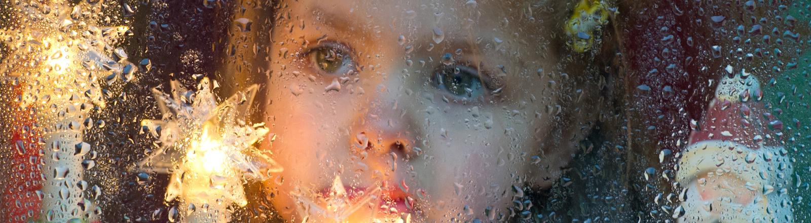 Die dreijährige Mia schaut am zweiten Weihnachtsfeiertag am 26.12.2013 aus einer vom Regen nassen Fensterscheibe in Sieversdorf (Brandenburg).