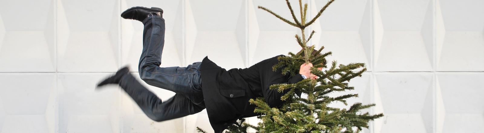 Ein Mann hät sich an einem Weihnachtsbaum fest