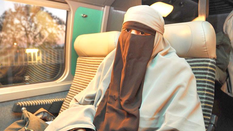 Eine Frau trägt in einem französischen Zug einen Nikab.