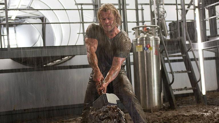 Filmszene: Der Schauspieler Chris Hemsworth als Thor; er steht in einer Art Fabrik und versucht einen Gegenstand aus einem großen Klumpen zu ziehen; ein kurzärmeliges T-Shirt zeigt seine extremen Armmuskeln, die angespannt sind (06.08.2020)