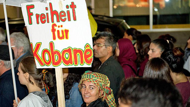 """Eine Frau hält am 09.10.2014 in der Nähe des Hauptbahnhofs in Stuttgart (Baden-Württemberg) im Rahmen einer kurdischen Demonstration gegen die islamistische Terrormiliz IS und die bedrohlichen Entwicklungen in der syrisch-türkischen Grenzstadt Kobane ein Schild mit der Aufschrift """"Freiheit für Kobane"""" in die Höhe."""