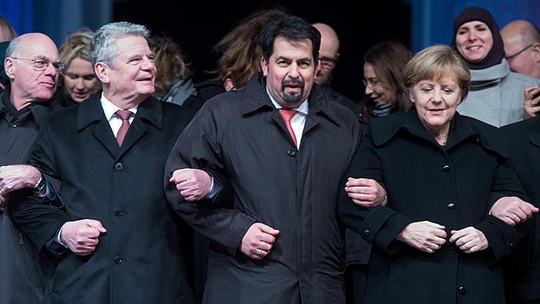Bundestagspräsident Norbert Lammer (CDU - l-r), Bundespräsident Joachim Gauck, der Vorsitzende des Zentralrates der Muslime in Deutschland, Aiman Mazyek, und Bundeskanzlerin Angela Merkel (CDU) hacken sich am 13.01.2015 bei einer Mahnwache für die Opfer der Anschläge in Frankreich vor dem Brandenburger Tor in Berlin unter.