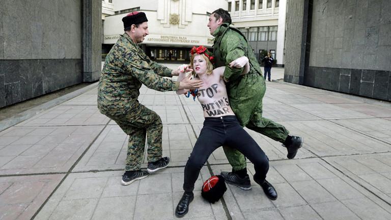 """Pro-russische Aktivisten zerren am 06.03.2014 eine halbnackte Femen-Aktivisten davon, sie trägt auf ihrem Oberkörper den Schriftzug: """"Stop Putins War"""""""