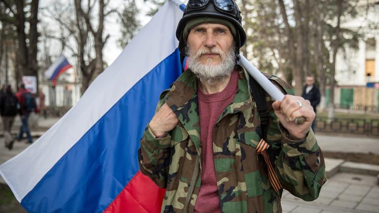 Ein älterer Mann mit der Fahne der Ukraine steht am 06.03.2014 vor dem Parlament in Simferopol, er trägt Helm und Militärjacke.