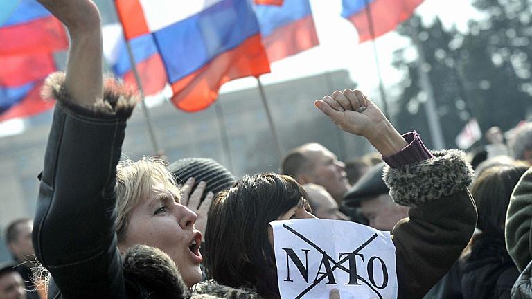 Bei einer Demo in Donetsk in der Ukraine hält eine Frau ein Schild mit dem durchgestrichenen NATO-Schriftzug hoch