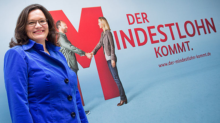 """Die Bundesministerin für Arbeit und Soziales, Andrea Nahles (SPD) steht am 02.04.2014 in Berlin vor einem Plakat mit der Aufschrift """"Der Mindestlohn kommt""""."""