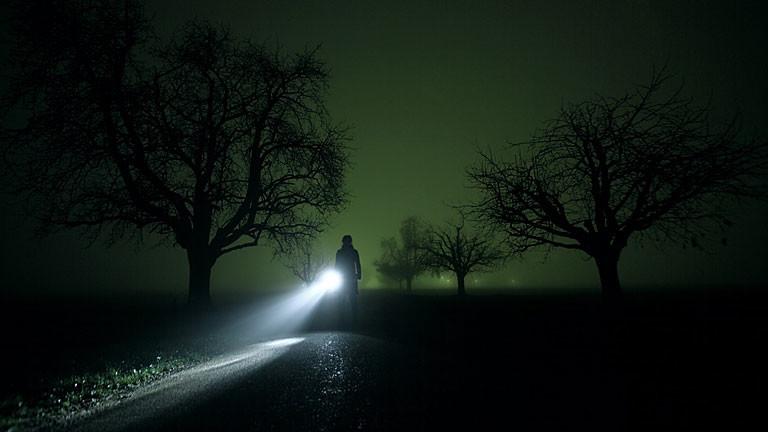 Eine Frau mit Taschenlampe leuchtet durch die Nacht