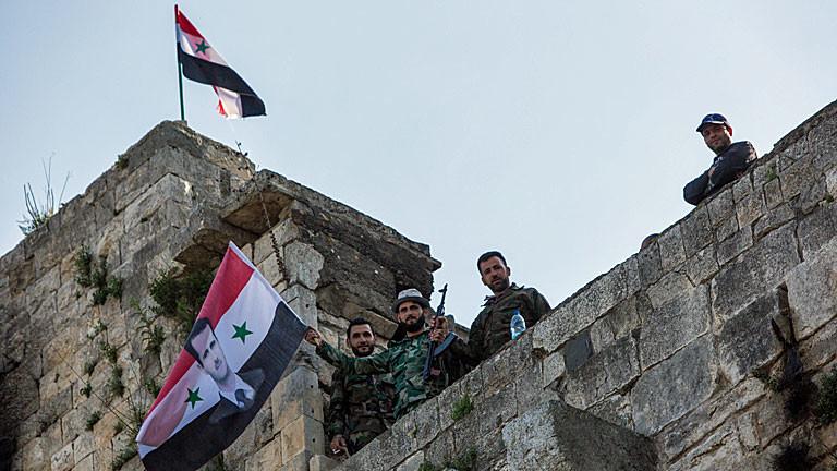"""Regimetreue Soldaten schwenken auf der syrischen Festung """"Krak des Chevaliers"""" die syrische Flagge mit dem Konterfei Assads."""