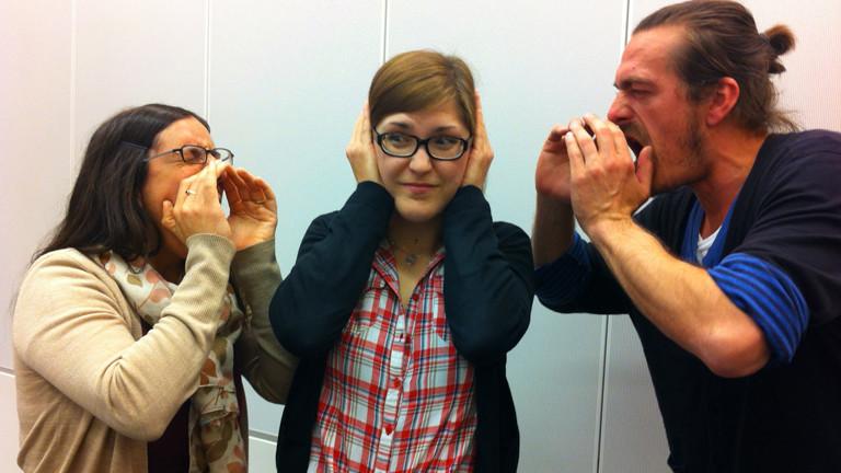 Die DRadio-Wissen-Praktikantin Friederike Seeger hält sich die Hände auf die Ohren, als sie von ihren Kollegen Nilofar Elhami und Till Haase angeschrien. wird.