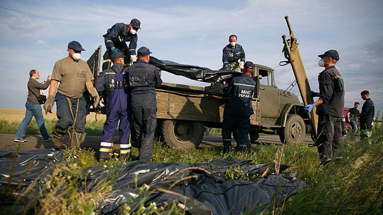 Hilfskräfte befördern an der Absturzstelle von Flug MH17 Leichensäcke auf einen LKW.