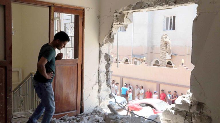 Ein Mann schaut durch ein Loch in der Hauswand nach einem Anschlag in der Nähe des Flughafens von Tripolis/Libyen.