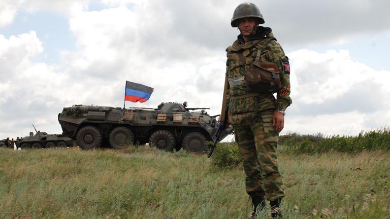 """Ein Soldat der Selbstverteidigungskräfte der """"Volksrepublik Donezk"""" steht vor einem Panzer in der Region um Donezk."""