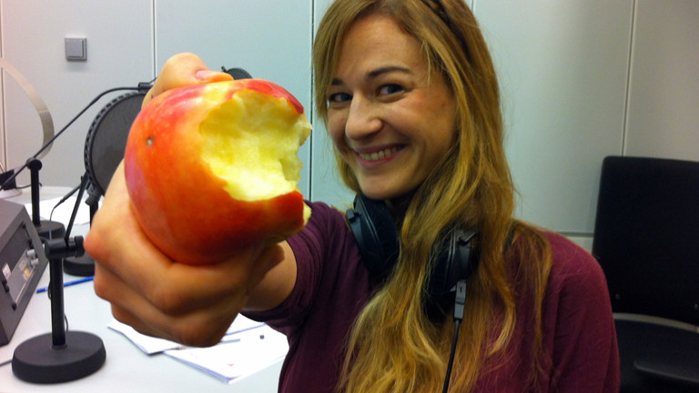 Anna Kohn präsentiert ihren angebissenen Apfel im DRadio-Wissen-Studio.