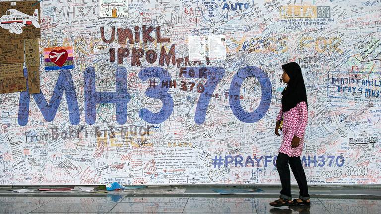 Eine junge Frau geht am 12.06.2014 auf dem Internationalen Flughafen Sepang nahe dem malysischen Kuala Lumpur an der Wand der Hoffnung für die Passagiere des vermisste Flugzeuges von MH370 vorüber