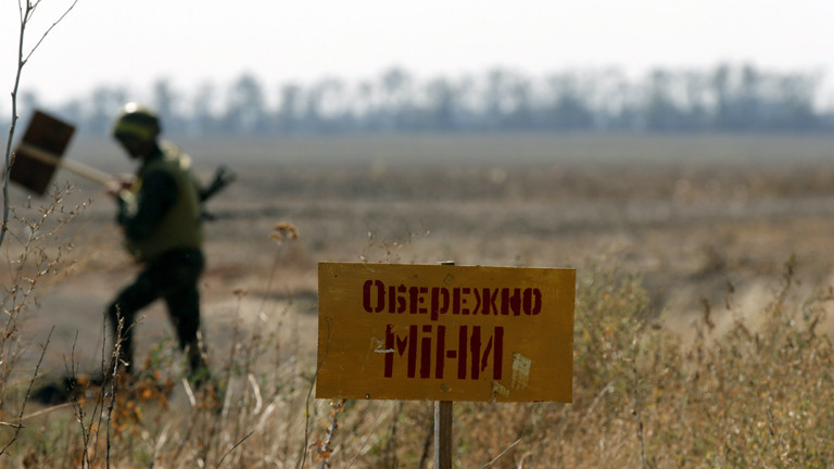 """Ein ukrainischer Soldat markiert am 06.09.2014 ein Gelände in der Nähe von Mariupol mit dem Schild """"Achtung Minen""""."""