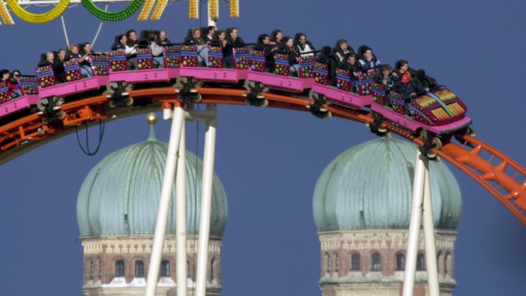 Vor der Kulisse der Münchner Frauentürme winkt ein Mann am Samstag (16.9.2000) aus dem Fahrgeschäft Olympia-Looping (dpa).