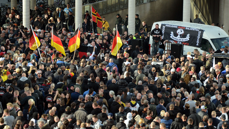 Demonstranten stehen am 26.10.2014 in Köln (Nordrhein-Westfalen) vor einem Fahrzeug mit einem Transparent der als gewaltbereit bekannten Gruppe «Hooligans gegen Salafisten» (HoGeSa). (dpa)