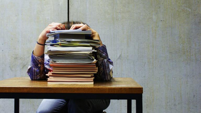Ein Student versteckt sich hinter einem Stapel Prüfungsunterlagen.
