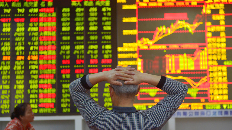 Die Börse in Hongkong: ein Broker schaut mit verschränkten Arme auf die digitale Anzeige.