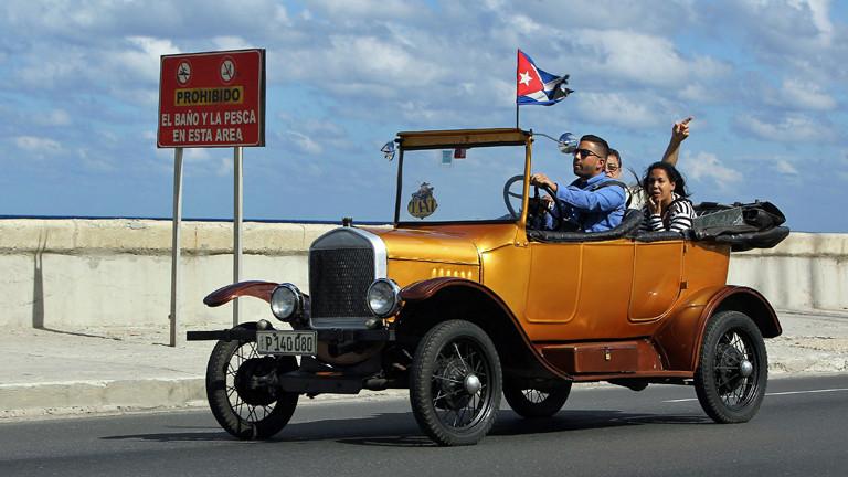Am 17.12.2014 fahren ein paar Leute in einem Oldtimer durch Havana in Kuba.