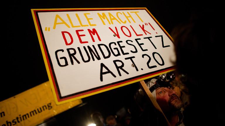 """Auf einer Pegida-Demo hält ein Demonstrant ein Schild: """"Alle Macht dem Volk! Grundgesetz Art. 20"""""""