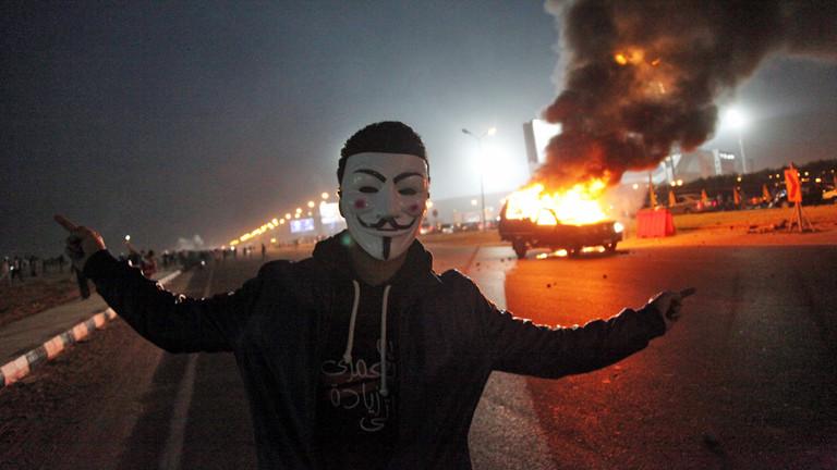 Ein Mann mit Anonymous-Maske steht vor einem brennenden Auto in Ägypten am 08.02.2015.