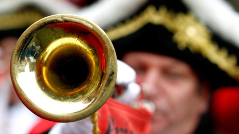 Ein Mann bläst zu Karneval in seine Trompete.