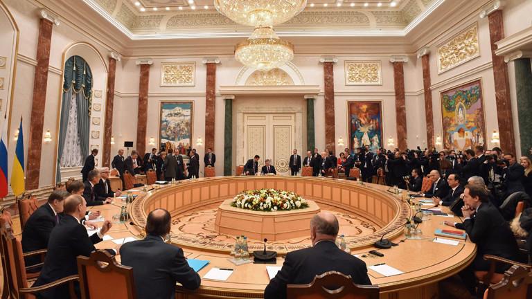 Kremlchef Wladimir Putin gestikuliert am 11.02.2015 im weißrussischen Minsk, während im Hintergrund Bundeskanzlerin Angela Merkel und der ukrainische Präsident Petro Poroschenko miteinander sprechen.