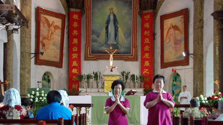 Zwei Frauen laufen am 12.08.2014 betend durch die Südkathedrale in Peking.