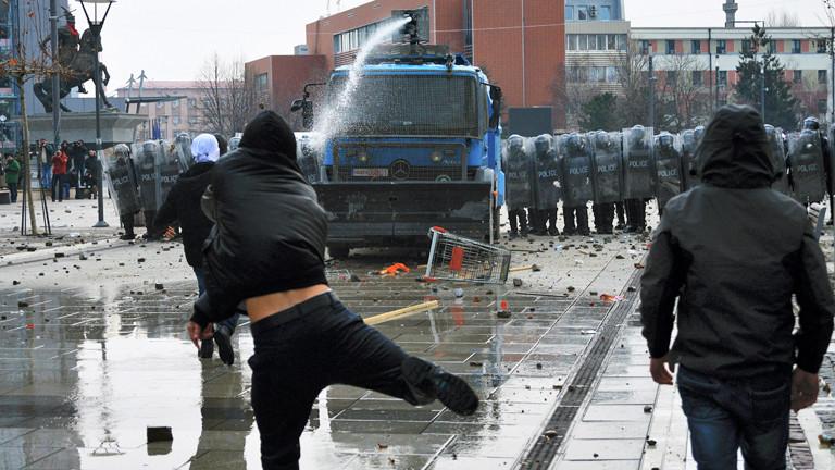 Demonstranten im Kosovo in Pristina stehen Polizisten und einem Wasserwerfer gegenüber.