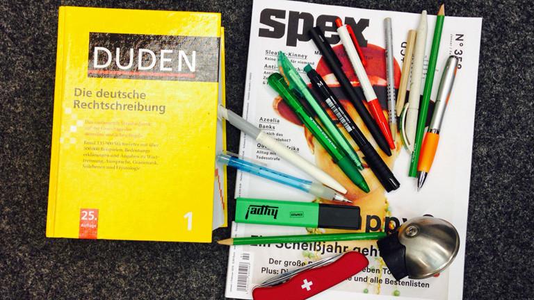 Auf dem Boden liegt ein Duden und ein Magazin, auf dem Stifte, ein Klappmesser und eine Fahrradklingel liegen.