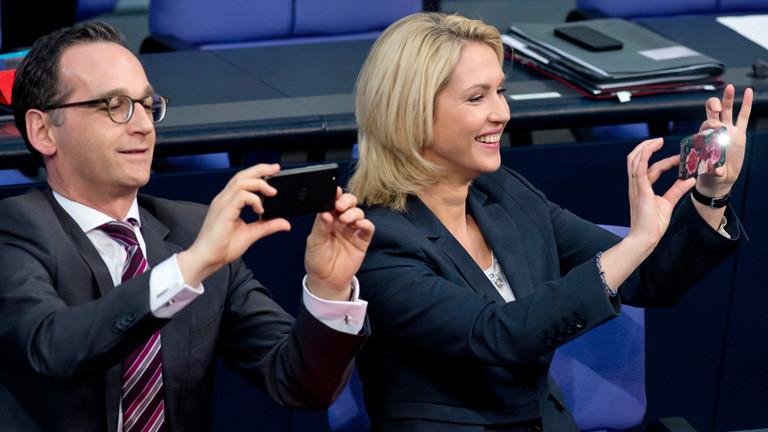 Die Bundesministerin für Familie, Frauen, Jugend und Senioren, Manuela Schwesig sitzt im Bundestag rechts neben Bundesjustizminister Heiko Maas. Beide fotografieren; Bild: dpa