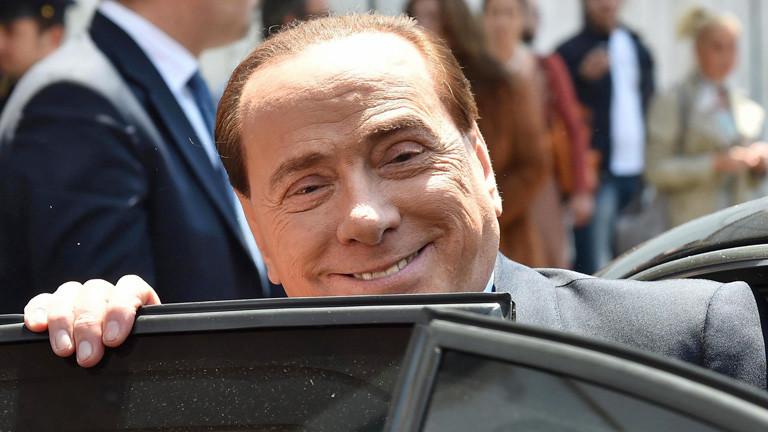 Silvio Berlusconi steigt in ein Auto ein und grinst in die Kamera (20. Mai 2014); Bild: dpa