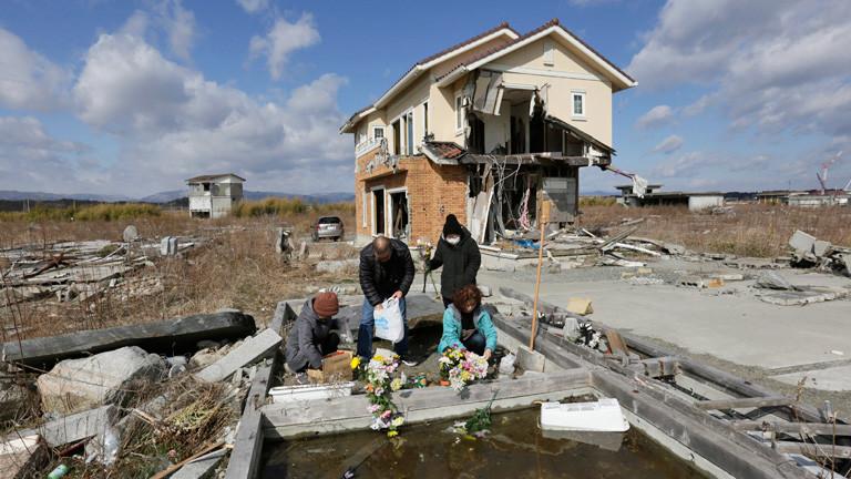 Vor einem zerstörten Haus legen vier Personen Blumen nieder. Eine Person trägt einen Mundschutz. Sie gedenken ihren getöteten Eltern in der Stadt Namie in der Präfektur Fukushima (11. März 2015); Bild: dpa