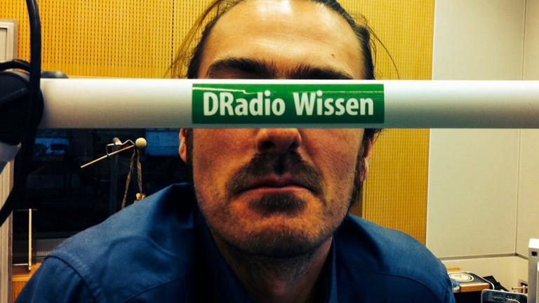 Moderator Till Haase versteckt sich hinter einem DRadio-Wissen-Schriftzug