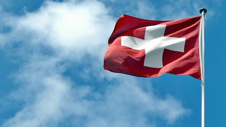 Die Flagge der Schweiz vor blauem Himmel.