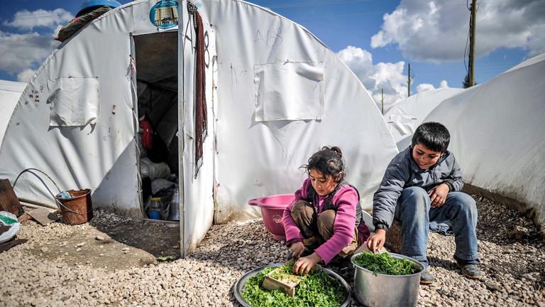 In einem syrischen Flüchtlingslager sitzen zwei Kinder vor einem Zelt und sind mit Lebensmitteln beschäftigt.