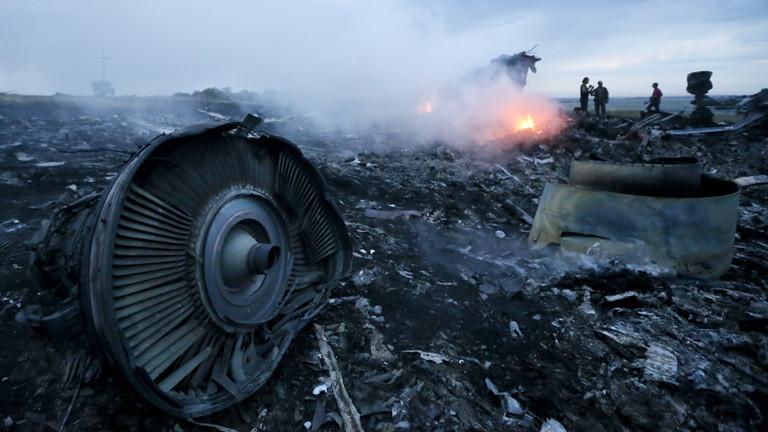 An der Absturzstelle der MH17 liegen Flugzeugteile, es qualmt und kleine Feuer brennen; Bild: dpa