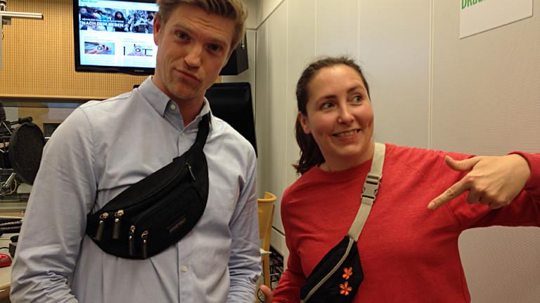 Thilo und Tina stehen im Studio und tragen beide Bauchtaschen.