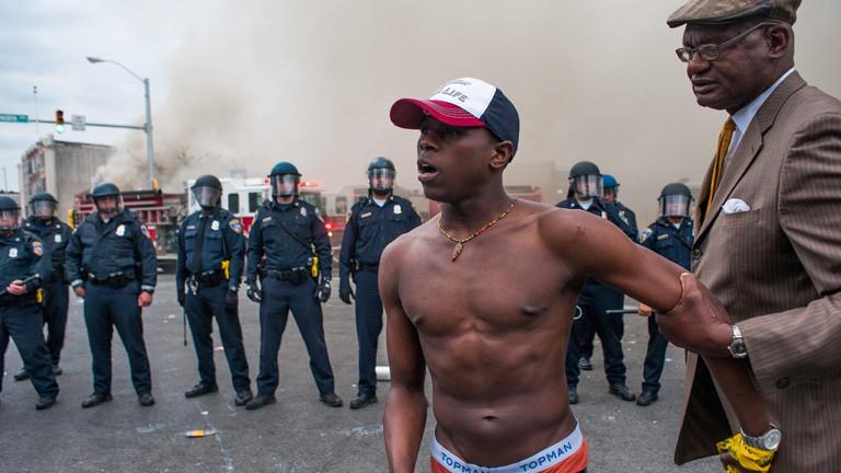 Ein Mann mit nacktem Oberkörper steht vor Polizisten. Er wird von einem älteren Mann zurückgehalten, in der US-Stadt Baltimore am 27.04.2015; Bild: dpa