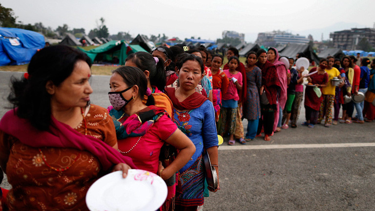 Frauen stehen in einer langen Schlange für Lebensmittel an. Viele halten Teller in der Hand. 8. Mai 2015 nach dem Erdbeben in Nepal; Bild: dpa