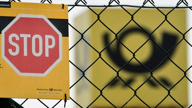 Ein STOP-Schild steht vor dem Zeichen der Deutschen Post.