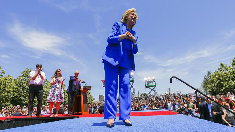 Hillary Clinton im blauen Hosenanzug auf einer Bühne. Sie hält ihre erste Wahlkampfrede; Bild: dpa