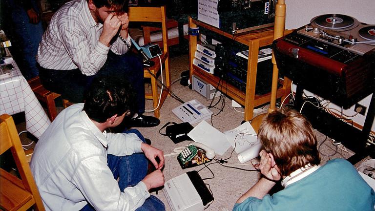 Auf dem Boden sitzen drei Entwickler des Fraunhofer Instituts zusammen. Zwischen ihnen steht unter anderem ein Telefon. Das Foto ist von 1992.