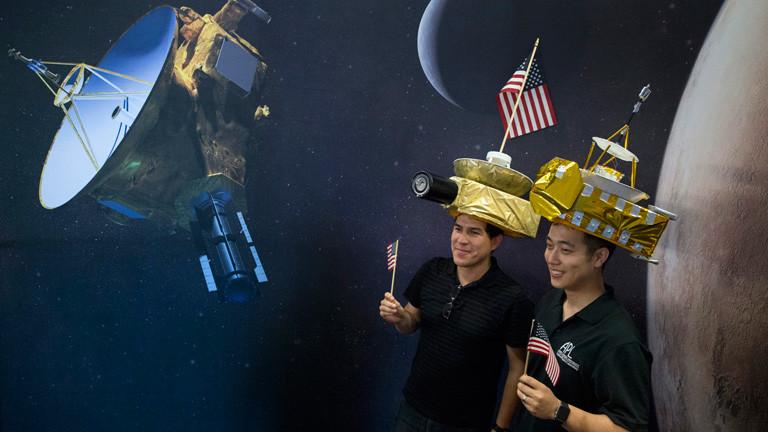 Zwei Wissenschaftler stehen mit einer nachgebauten Sonde auf dem Kopf vor einem Planeten-Nachbau.