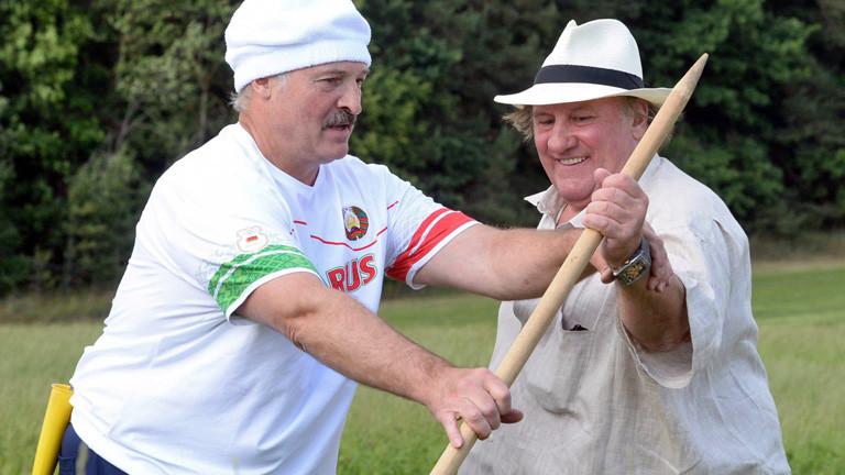 Gerard Depardieu und Alexander Lukaschenko stehen eng beieinander und halten zusammen ein Gartengerät; Bild: dpa