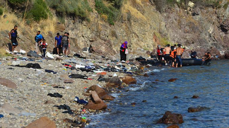 Menschen auf einem Boot kommen am Strand an.