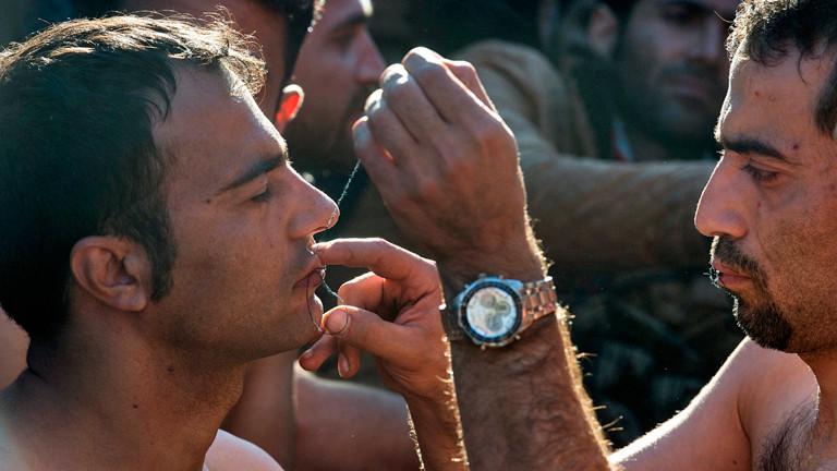Ein iranischer Flüchtling vernäht einem anderen die Lippen.